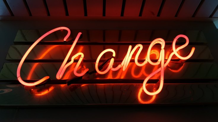 Red neon sign saying Change